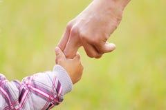 El padre lleva a cabo la mano de un pequeño niño Imagen de archivo libre de regalías