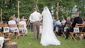 El padre lleva a la novia a preparar en la boda, hija de la guía del papá en el vestido blanco al futuro marido en la boda,