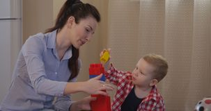 El padre muestra a niño cómo jugar con los bloques de la construcción y tener tiempo de la diversión junto almacen de video