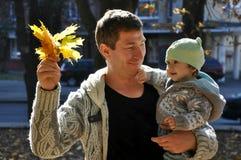 El padre muestra a niño las hojas otoñales fotos de archivo libres de regalías