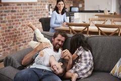 El padre Plays With Children como madre trabaja en el ordenador portátil fotos de archivo libres de regalías