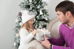 El padre presenta a regalo su hija en el tiempo de la Navidad Foto de archivo