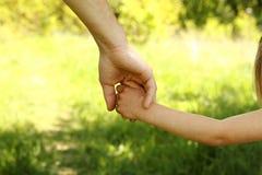 El padre que lleva a cabo la mano de un pequeño niño Fotos de archivo libres de regalías
