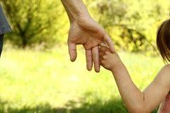El padre que lleva a cabo la mano de un pequeño niño Foto de archivo libre de regalías
