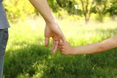 El padre que lleva a cabo la mano de un pequeño niño Imágenes de archivo libres de regalías