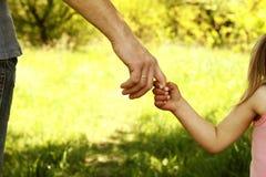 El padre que lleva a cabo la mano de un pequeño niño Imagen de archivo libre de regalías
