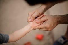 El padre que lleva da llevar a cabo una pequeña mano del hijo con los rasguños Fotos de archivo