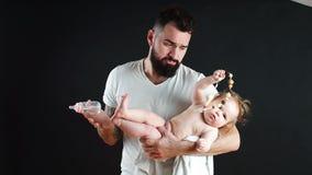 El padre que se sostiene encendido da el pequeño bebé lindo Concepto de la familia, del amor y de la felicidad metrajes