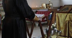 El padre santo está rogando en la iglesia ortodoxa almacen de metraje de vídeo
