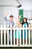 El padre sonriente, la madre y la pequeña hija agitan sus manos Fotos de archivo libres de regalías