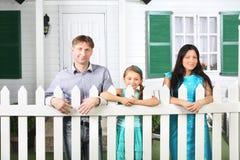 El padre sonriente, la madre y la pequeña hija se colocan al lado de la cerca Imagen de archivo