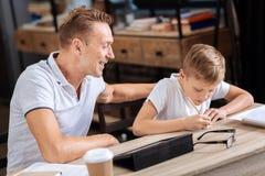 El padre sonriente que mira a su hijo escribe una nota Imagen de archivo libre de regalías