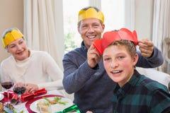El padre sonriente que pone el sombrero del partido en hijos dirige Foto de archivo