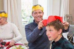 El padre sonriente que pone el sombrero del partido en hijos dirige Imagen de archivo libre de regalías
