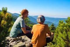 El padre sonriente y su hijo adolescente admiran las montañas Fotografía de archivo