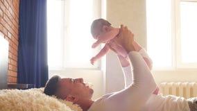 El padre sostiene el canal del hijo en casa el sol tener el papá de risa juguetón de la diversión almacen de metraje de vídeo
