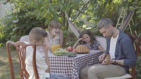 El padre toca la guitarra para su familia en una tabla de cena que se sienta en el patio trasero Relaciones de familia amistosas almacen de metraje de vídeo