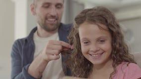 El padre trenza la coleta de la muchacha, sonriendo El tiempo del gasto del hombre con su pequeña hija linda Familia feliz, una almacen de metraje de vídeo