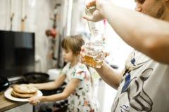 El padre vierte la miel en el cuenco y su pequeña hija toma una placa con las crepes en la cocina fotos de archivo libres de regalías