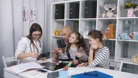 El padre y dos hijas en la oficina del doctor para el consejo El padre trajo a sus hijas al doctor para a metrajes
