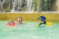 El padre y dos muchachos nadan en la piscina Familia feliz que juega en el agua azul de la piscina en un centro turístico tropica Foto de archivo libre de regalías