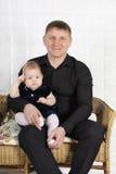 El padre y el bebé jovenes felices se sientan en el sofá. Fotos de archivo