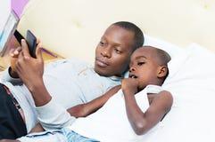 El padre y el hijo consulta un teléfono móvil en cama Foto de archivo