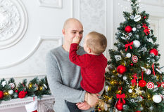 El padre y el hijo contra la perspectiva de un árbol de navidad Fotos de archivo libres de regalías