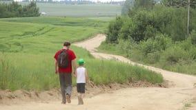 El padre y el hijo descienden de las montañas cerca del campo metrajes
