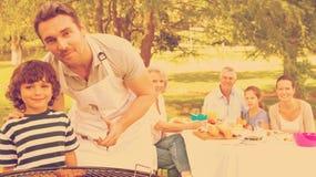 El padre y el hijo en la barbacoa asan a la parrilla con la familia que almuerza en parque Fotografía de archivo