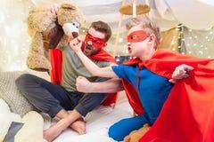 El padre y el hijo en super héroe viste jugar con el oso de peluche en el fuerte combinado Foto de archivo
