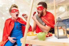 El padre y el hijo en super héroe viste la consumición de las fresas en el fuerte combinado Fotografía de archivo