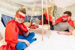 El padre y el hijo en super héroe viste la consumición de las frutas en el fuerte combinado Imagenes de archivo