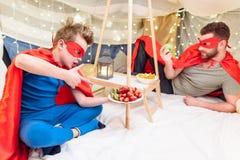 El padre y el hijo en super héroe viste la consumición de las frutas en el fuerte combinado Foto de archivo