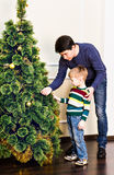 El padre y el hijo están adornando el árbol de navidad Imágenes de archivo libres de regalías