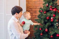 El padre y el hijo están adornando el árbol de navidad Fotografía de archivo