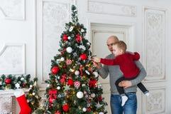 El padre y el hijo están adornando el árbol de navidad Fotografía de archivo libre de regalías