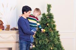 El padre y el hijo están adornando el árbol de navidad Foto de archivo