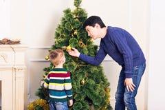El padre y el hijo están adornando el árbol de navidad Fotos de archivo