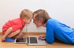 El padre y el hijo están en conflicto sobre la almohadilla táctil y el ordenador Fotos de archivo libres de regalías