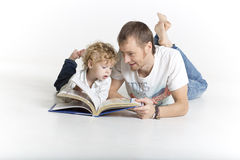 El padre y el hijo están leyendo un libro en el piso Imagen de archivo libre de regalías