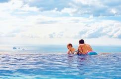 El padre y el hijo felices disfrutan del paisaje marino hermoso de la piscina del infinito, concepto de las vacaciones Foto de archivo