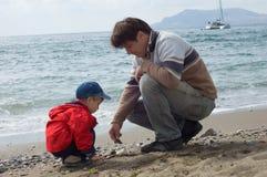 El padre y el hijo felices juegan en la playa Imágenes de archivo libres de regalías