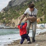 El padre y el hijo felices juegan en la playa Imagen de archivo