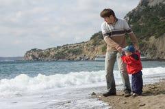 El padre y el hijo felices juegan en la playa Fotografía de archivo libre de regalías
