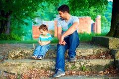 El padre y el hijo hablan, mientras que se sienta en las escaleras viejas entre árboles Imagen de archivo