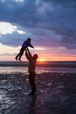 El padre y el hijo juegan en la playa en puesta del sol, tiro de la silueta Imagen de archivo