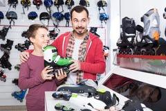 El padre y el hijo que deciden sobre nuevo patina sobre ruedas en tienda de los deportes Fotografía de archivo
