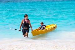 El padre y el hijo que gozan del kajak montan en la playa troical Imágenes de archivo libres de regalías