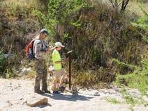 El padre y el hijo que miran un mapa y piensan y los indicadores en donde Fotografía de archivo libre de regalías